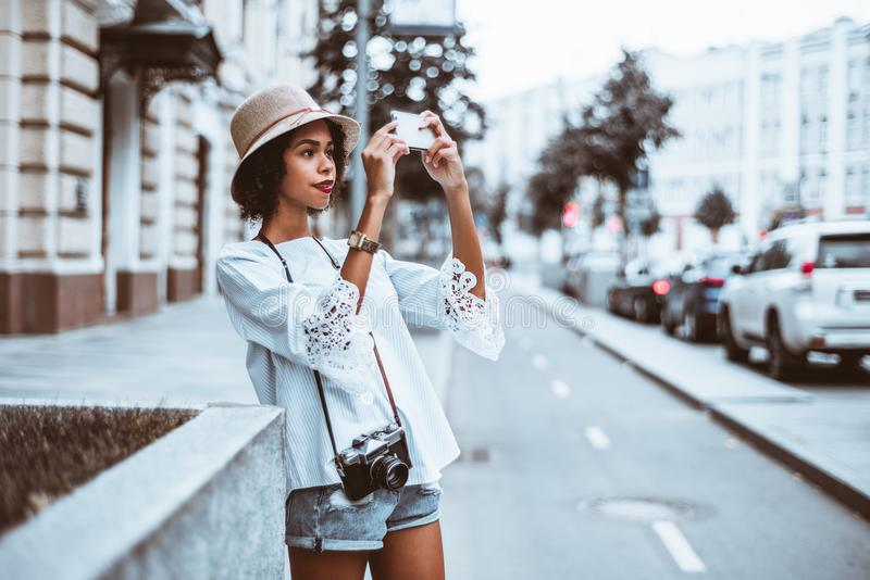 Brasiliansk flicka som fotograferar på gatan via hennes mobiltelefon royaltyfria foton