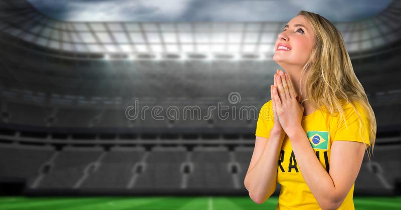 Brasiliansk fotbollfan som ber och hoppas i stadion för seger fotografering för bildbyråer