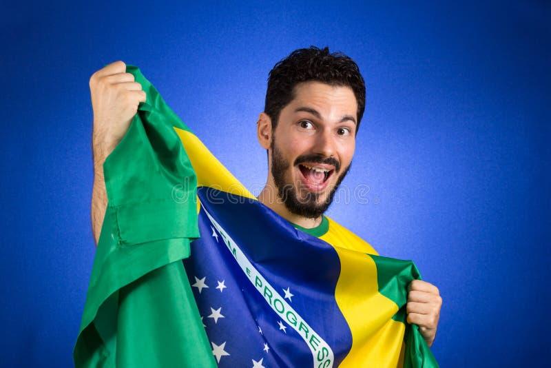 Brasiliansk fotbollfotbollsspelare som rymmer den Brasilien flaggan royaltyfria foton