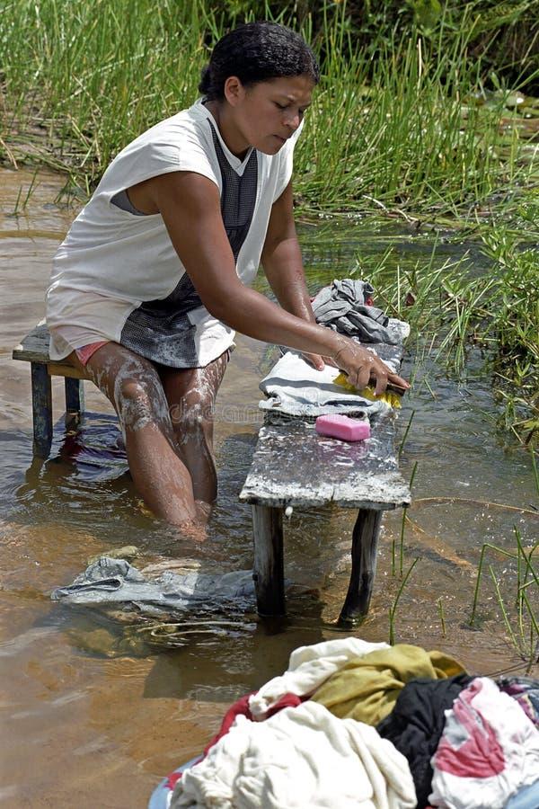 Brasiliansk kvinnatvagningkläder i floden, Brasilien fotografering för bildbyråer
