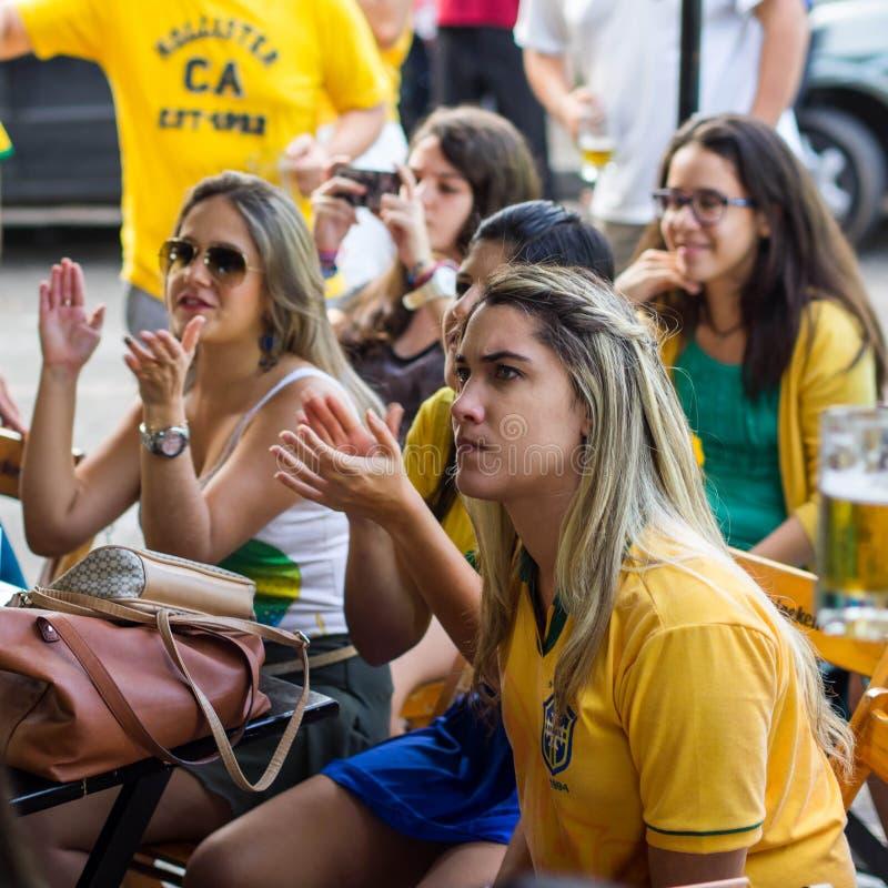 Brasilianska flickor som håller ögonen på världscupen att matcha på TV på en stång royaltyfria foton