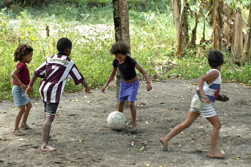 Brasilianska pojkar och flickor som spelar fotboll i tropisk värme arkivfoton