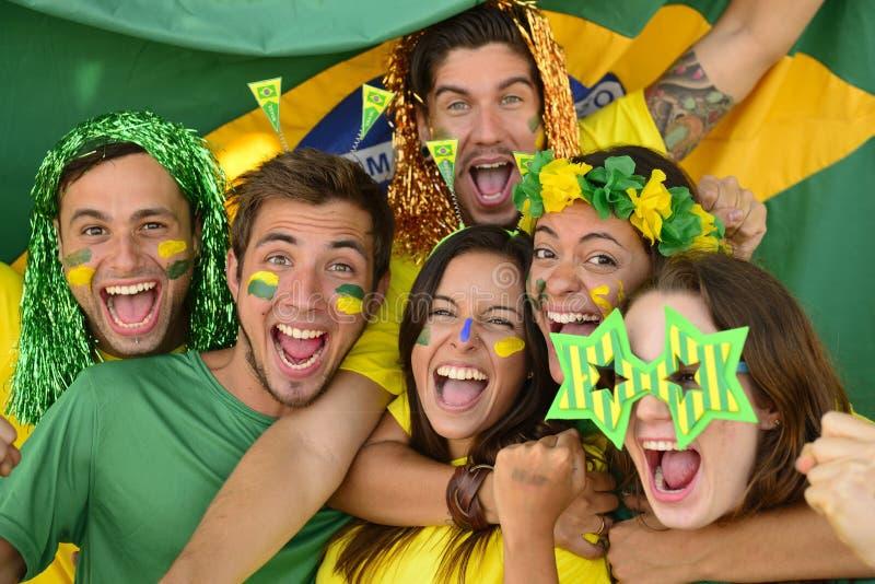 Brasilianska sportfotbollfans som firar seger tillsammans. arkivfoton