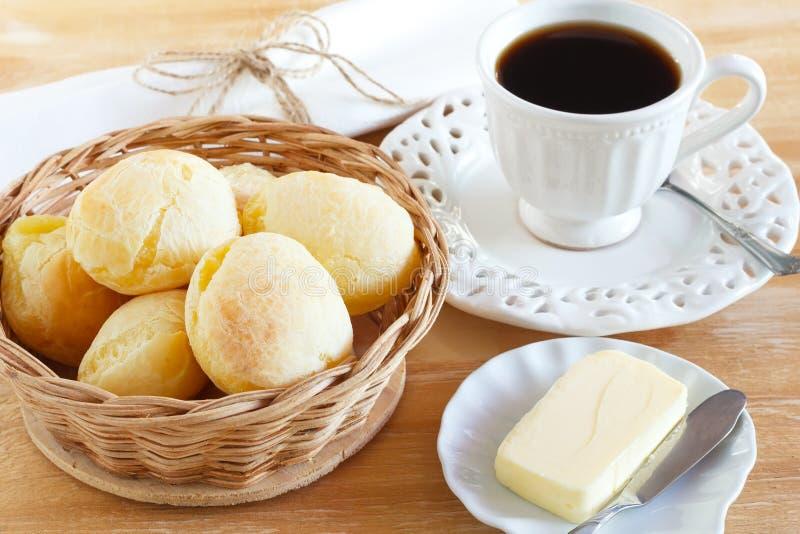 Brasilianskt mellanmålostbröd (pao de queijo) med koppen kaffe royaltyfri foto