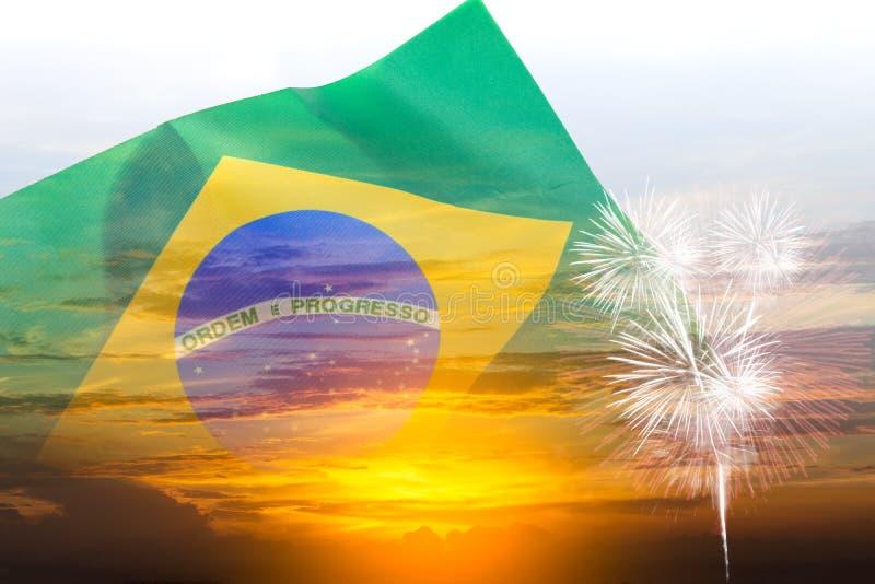 Brasilien självständighetsdagenbegrepp av dubbel exponering som vinkar den Brasilien flaggan och solnedgånghimmel med fyrverkerie royaltyfri foto