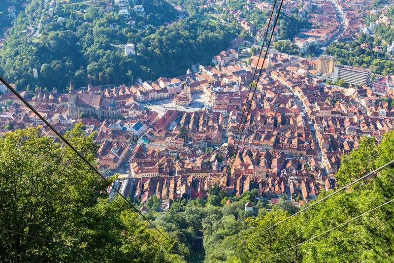 Brasov historisk stadsmitt som ses av turister från bilen för monteringsTampa kabel Medeltida stad i en dal - höga tornspiror och royaltyfria foton