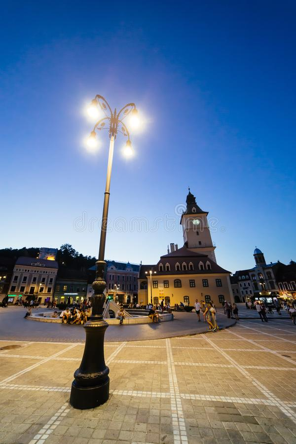 BRASOV, ROMANIA - AUGUST 1, 2017: People on central council square (Piata Sfatului) with town hall clock tower on summer evening. City blue hour life scene stock photo