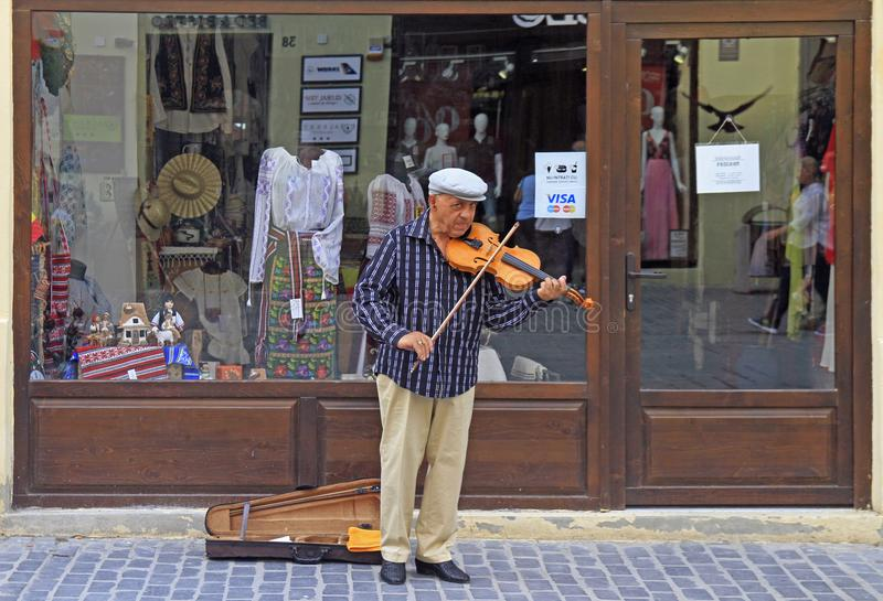 Street musician is playing violin outdoor in Brasov, Romania royalty free stock images