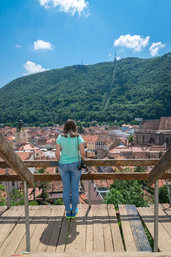 BRASOV, ROMANIA - 19 JUNE, 2018: Girl admiring the city viewed from White Tower in Brasov, Romania royalty free stock images