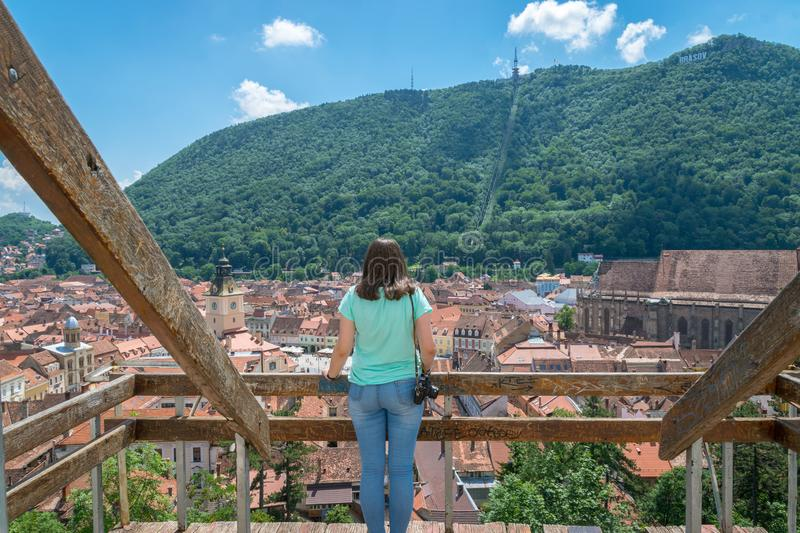 BRASOV, ROMANIA - 19 JUNE, 2018: Girl admiring the city viewed from White Tower in Brasov, Romania royalty free stock photo