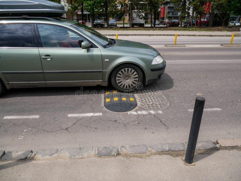 Passing car on street bump close up shot. Brasov, Romania- 04 May 2019: Passing car on street bump close up shot stock photography