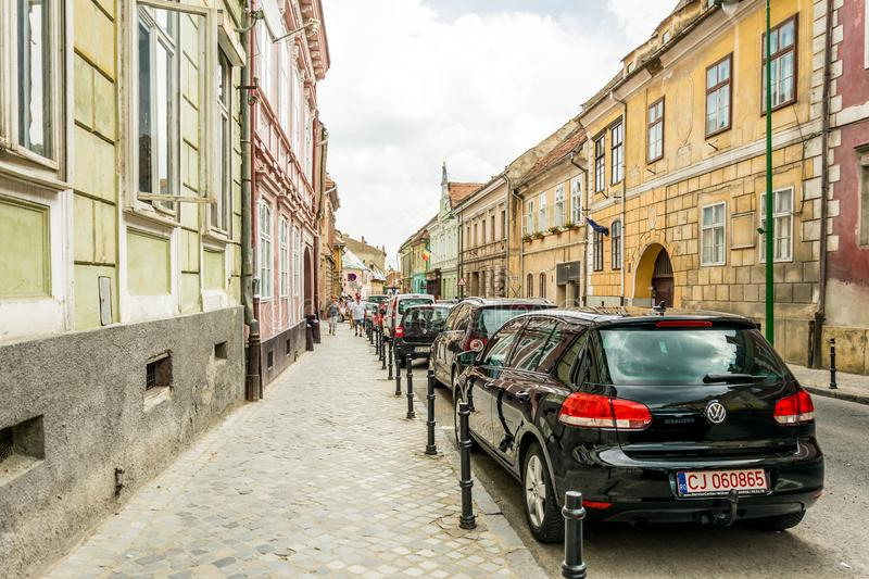 Colorful narrow streets of the medieval European city of Brasov in Romania and cars stock photos