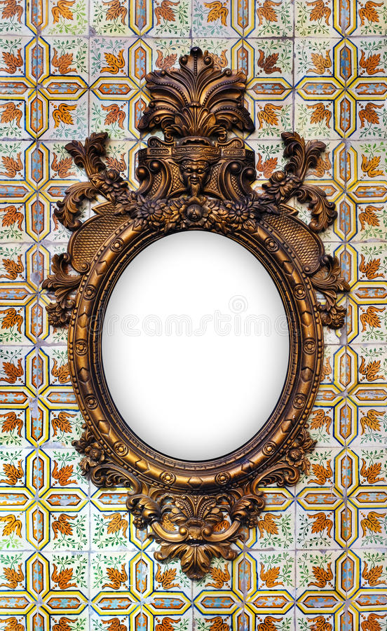 Brass Baroque Frame. Beautiful and complex brass baroque frame hanged on a tiled wall royalty free stock photography