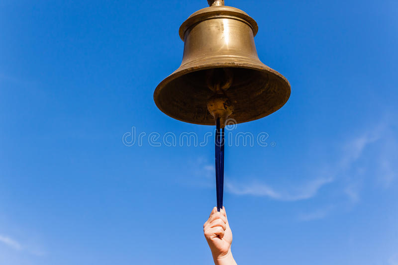 Brass Bell Hand. Brass bell with hand closeup ringing sound notice tool instrument royalty free stock photos