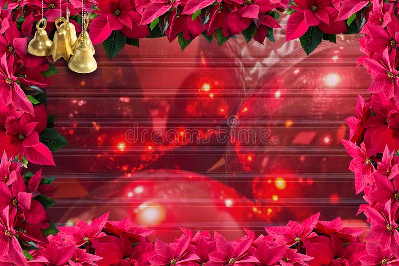 Brass bells and red poinsettia Christmas flower frame. Background and blur of red ornaments on corrugated texture copy space stock photography