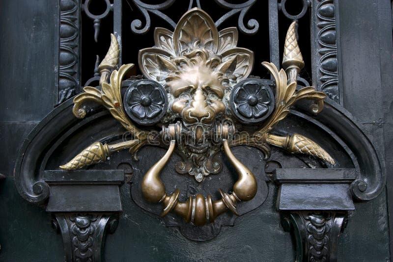 Brass brown knocker in a green door stock images