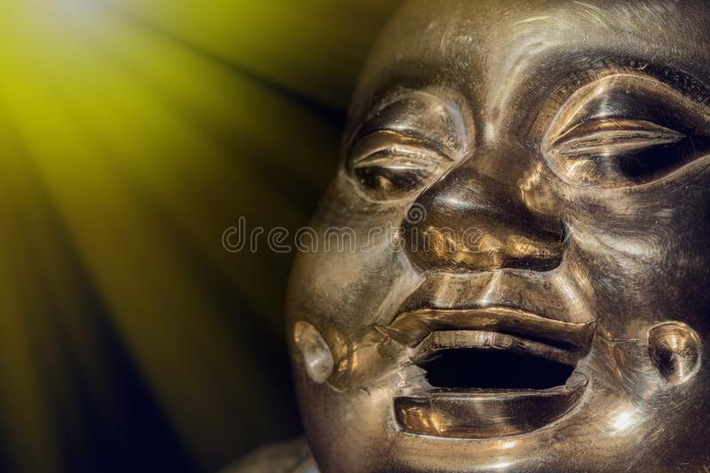 Brass buddha. Happy laughing enlightened monk face. Brass buddha. Happy laughing spiritually enlightened monk face in close-up against black background with copy royalty free stock photos
