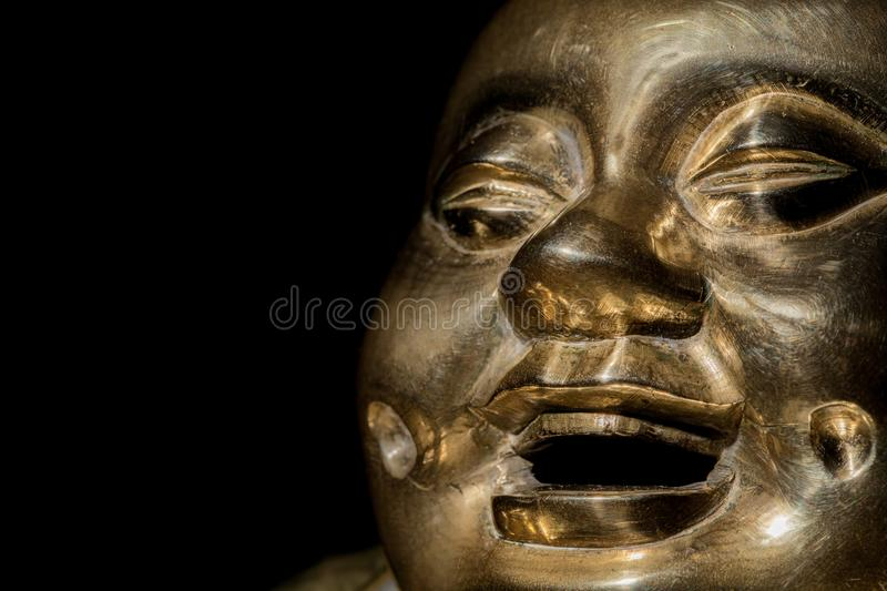 Brass buddha. Happy laughing monk face in close-up royalty free stock photography