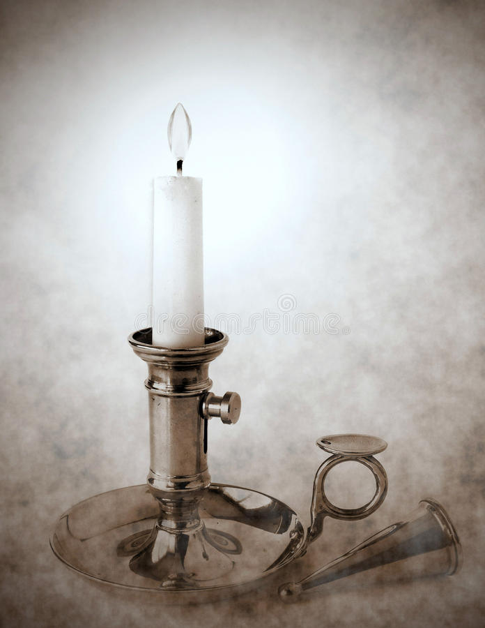 Brass candlestick with snuffer. Vintage brass candlestick with burning candle and snuffer, vignette and duotone effect stock photo