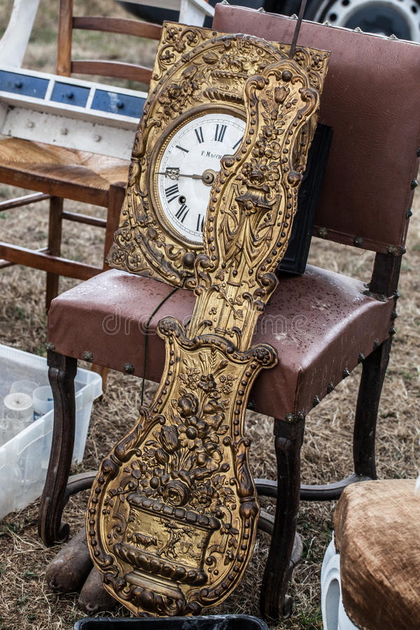 Brass clock in parts for clock connoisseur. Display of old clock parts in brass and rustic chairs sold at flea market for antique and vintage collections royalty free stock image