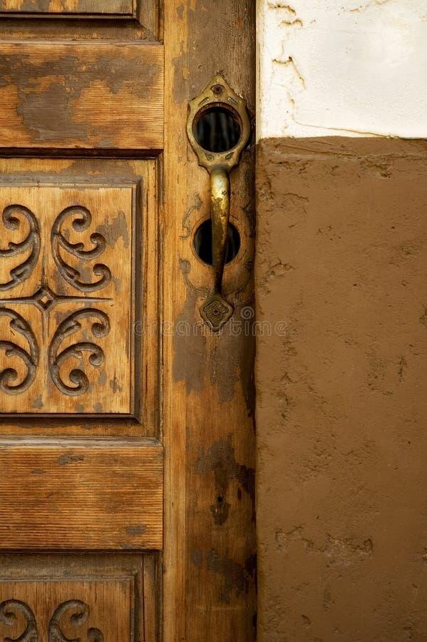 Brass Door Handle. On spanish style carved door stock photos
