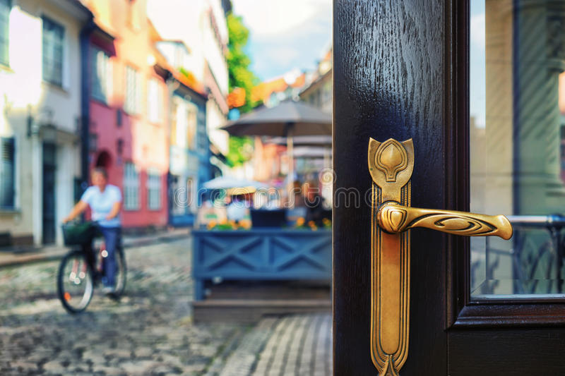 Brass door handle on the background of the street. With a passing woman on a bicycle around the summer restaurant in the old colored houses stock images