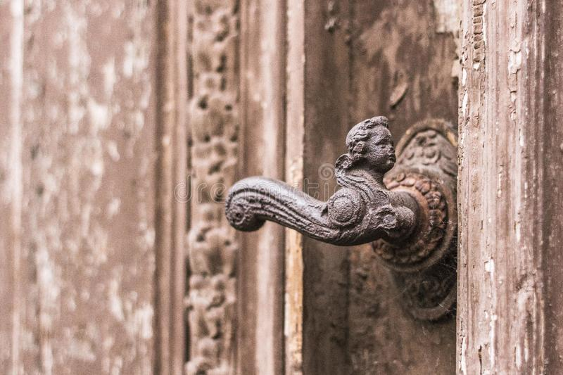 Brass door handle in the form of an angel face stock photos