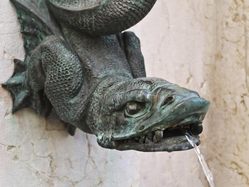Gekofish fountain. Brass faded to green gekofish themed fountain head spouts water.  scales stock photography