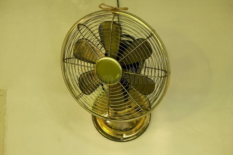 Brass fan on white wall. Old brass fan mounted on a white wall. Retro style for home decor royalty free stock images