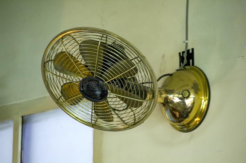 Brass fan on white wall. Old brass fan mounted on a white wall. Retro style for home decor royalty free stock photography