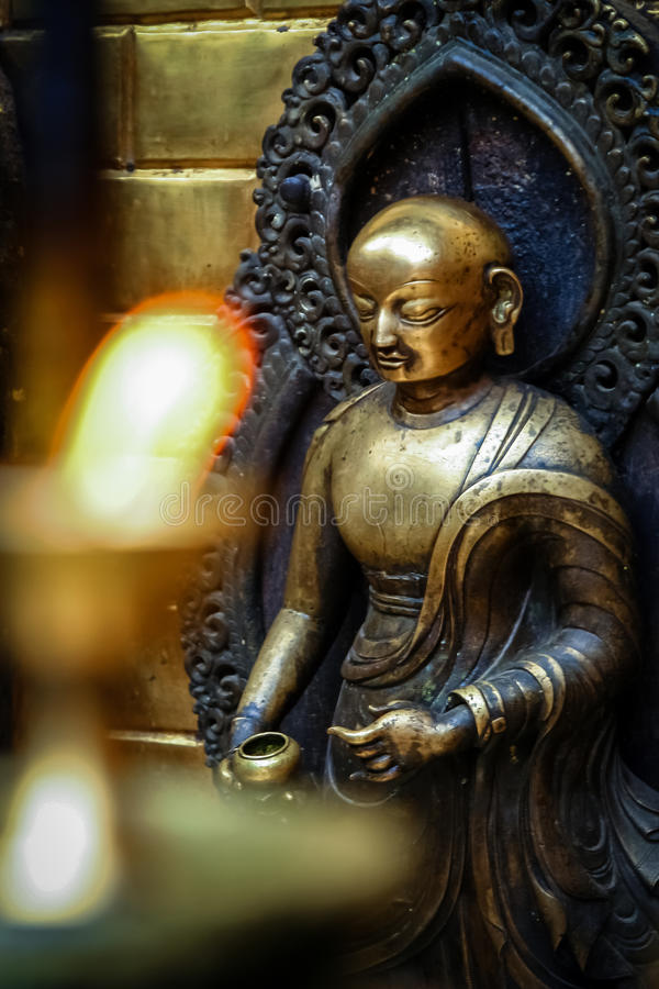 Brass figurine in a temple. Brass figurine of a deity and candles burning inside one of the Buddhist temples in Nepal royalty free stock photography
