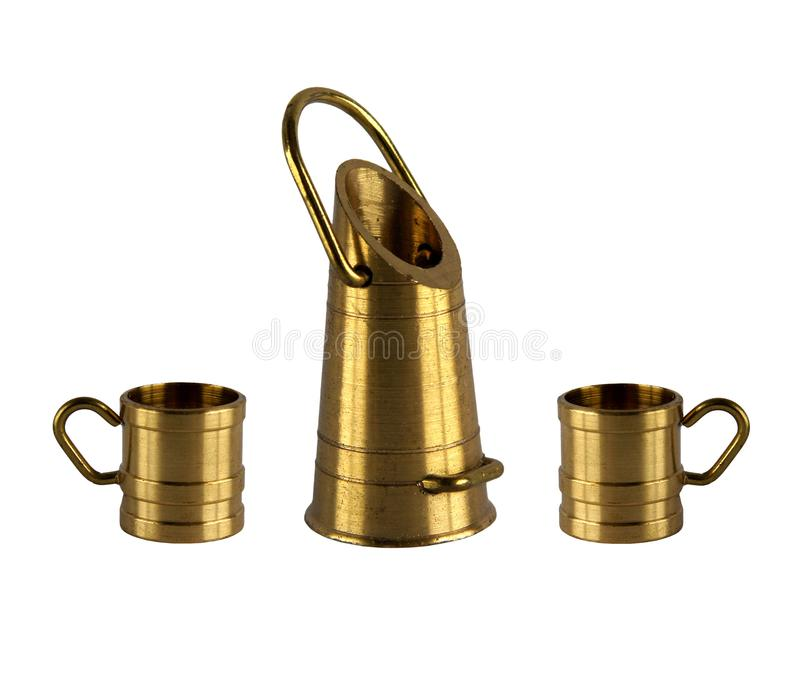 Vintage brass bucket and mugs. Brass figurines or miniatures of vintage bucket and two mugs isolated on white background royalty free stock photo