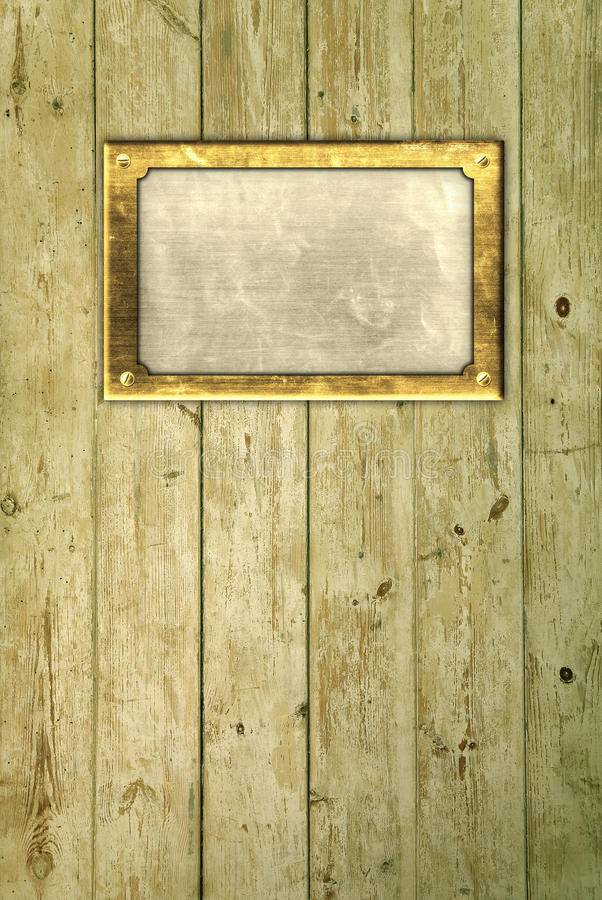 Brass frame on floorboards. Brass nameplate on distressed floorboards stock image