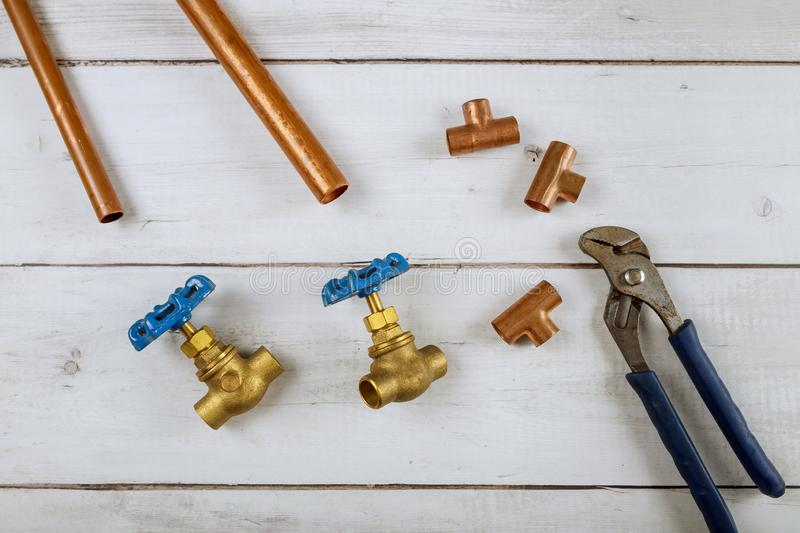 Brass gate valve, monkey wrench brass plumbing fittings on wooden background. Brass gate valve on wooden background, monkey wrench brass plumbing fittings royalty free stock images