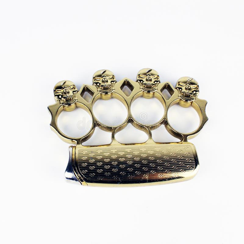 Brass knuckle duster, weapon for hand, isolated on white. Design, gangster. Brass knuckle duster with golden skull, weapon for hand, isolated on white background stock image