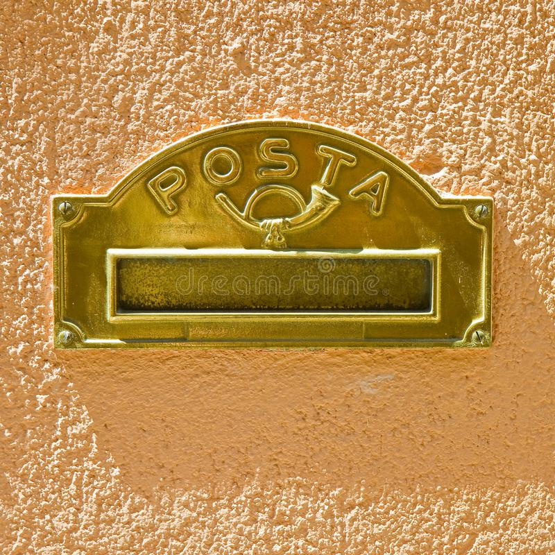 Brass mail box built into a colored plaster wall royalty free stock image