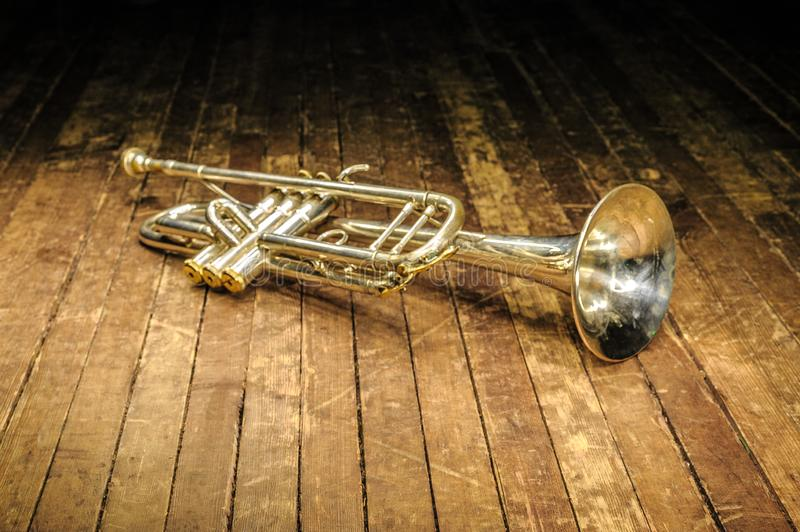 White brass trumpet lies on a wooden stage stock image