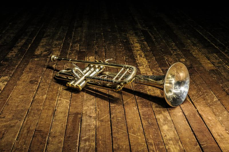 White brass trumpet lies on a wooden stage in the dark royalty free stock photo