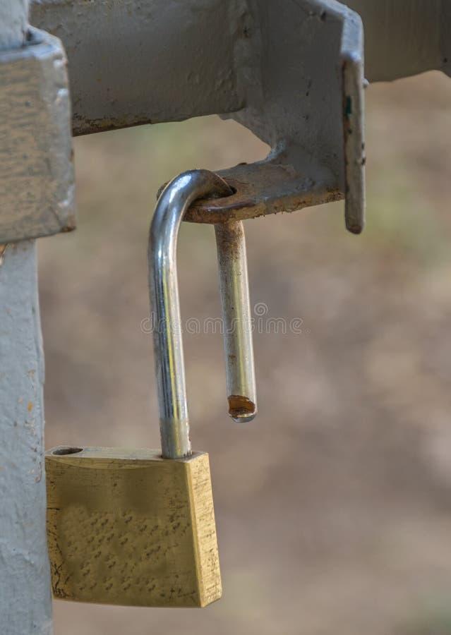 An open padlock hangs on a gate stock photo