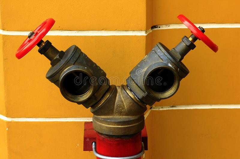 Red Valves for Fire Extinguishers. Brass pipe with red valve for supplying fire water on the road royalty free stock photos