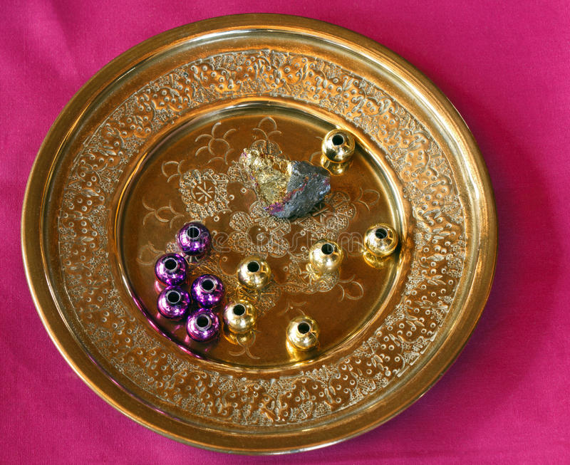 Brass Plate with assorted beads. In Madi Gras colors. GOld Pyrite rock with Fuschia striations stock image