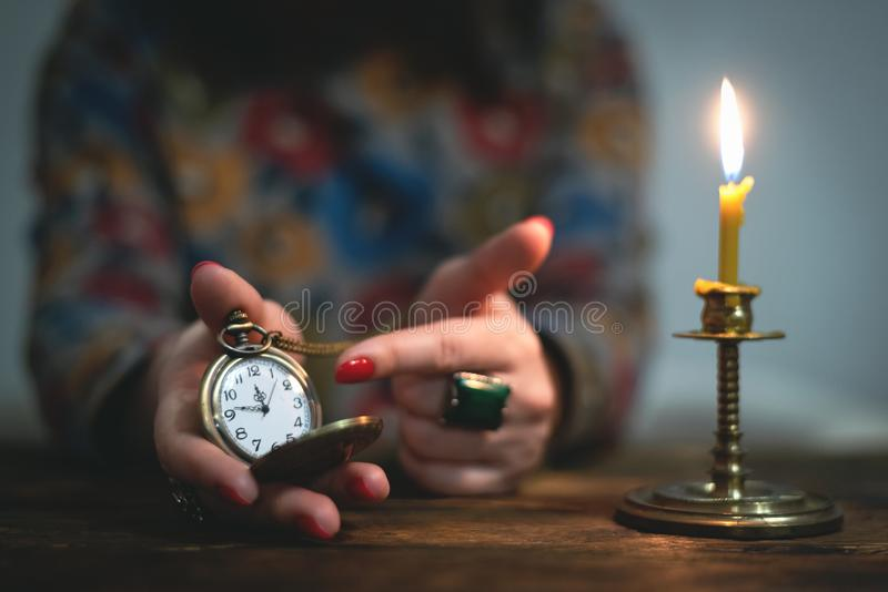 Brass pocket watch. Brass pocket watch with arrows on a almost twelve o clock in a hand of a woman. Time to tell a secrets or go bed to sleep stock photography
