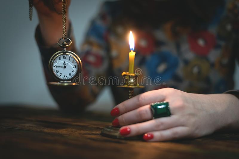 Brass pocket watch. Brass pocket watch with arrows on a almost twelve o clock in a hand of a woman. Time to tell a secrets or go bed to sleep. Divination for royalty free stock photography