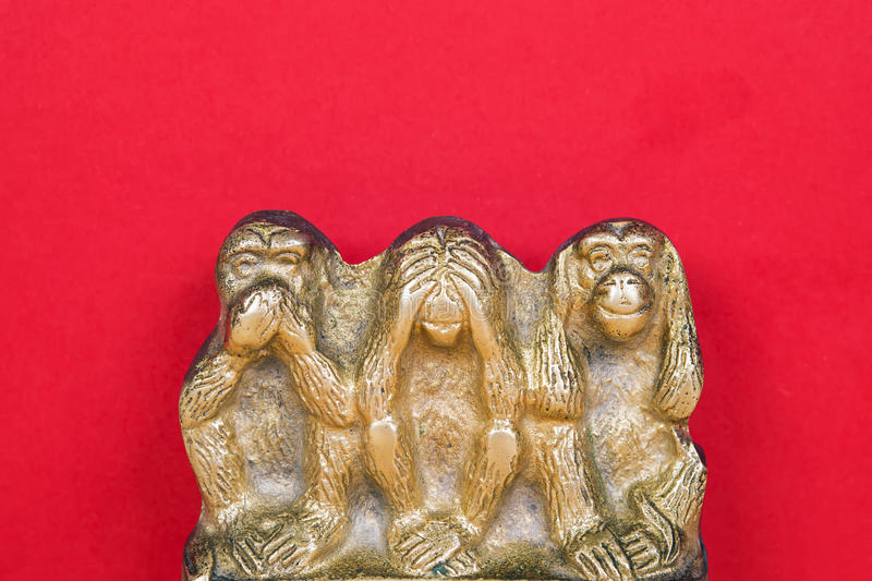 Brass statue of three monkeys isolated on wooden surface. Souvenir figurines of the three monkeys, symbolizing the Buddhist idea of non-doing of evil royalty free stock photos