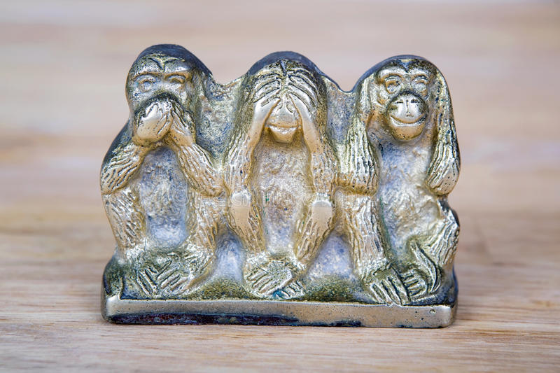 Brass statue of three monkeys isolated on wooden surface. Souvenir figurines of the three monkeys, symbolizing the Buddhist idea of non-doing of evil stock photos
