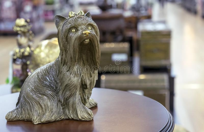 Brass statuette of the Yorkshire Terrier on a round wooden table.  royalty free stock photography
