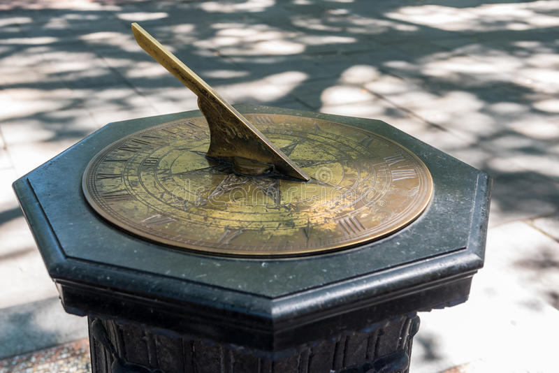 Brass Sundial on a stone stand. Old brass sundial on a stone or marble column on the corner of a sidwalk royalty free stock photography