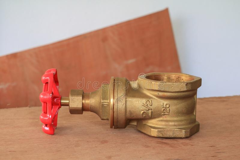 Brass valve with red knob in a factory plumber on wooden floor background.  royalty free stock photos