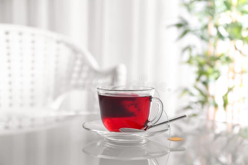 Brassage de la boisson chaude avec le sachet à thé dans la tasse en verre sur la table photo stock