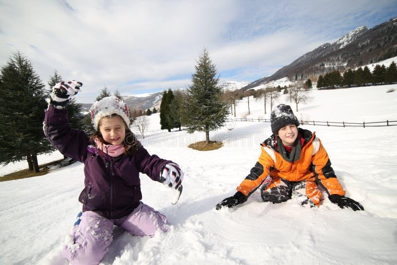 Brat i siostra bawić się w śniegu w zimie zdjęcia royalty free